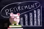 Pink piggy bank with glasses standing on books next to a blackboard with retirement savings message. Sharp focus on the piggy bank with blackboard slightly blurred.