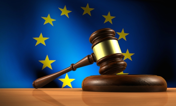 European Union law legislation and parliament concept with a 3d rendering of a gavel on a wooden desktop and the EU flag on background.